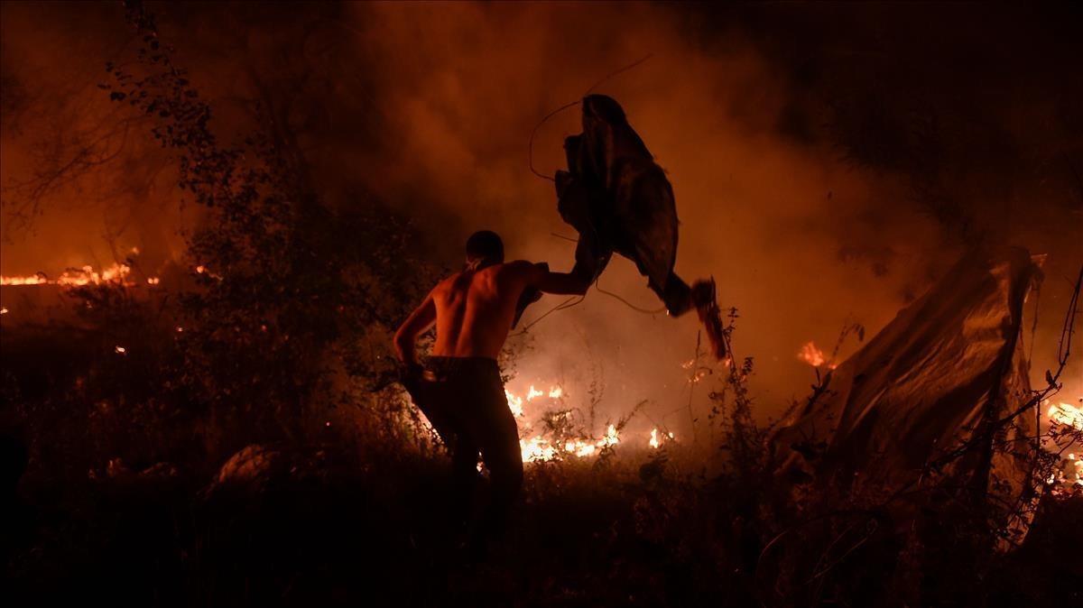 Un joven intenta sofocar el fuego con loque puede.