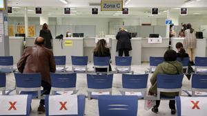 Funcionarios atienden a algunos usuarios en la Agencia Tributaria en Barcelona.