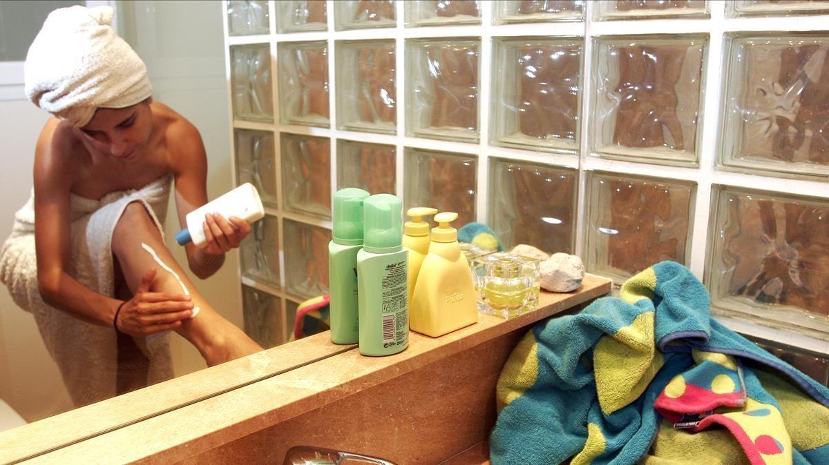 Una mujer se aplica 'aftersun' en el baño.