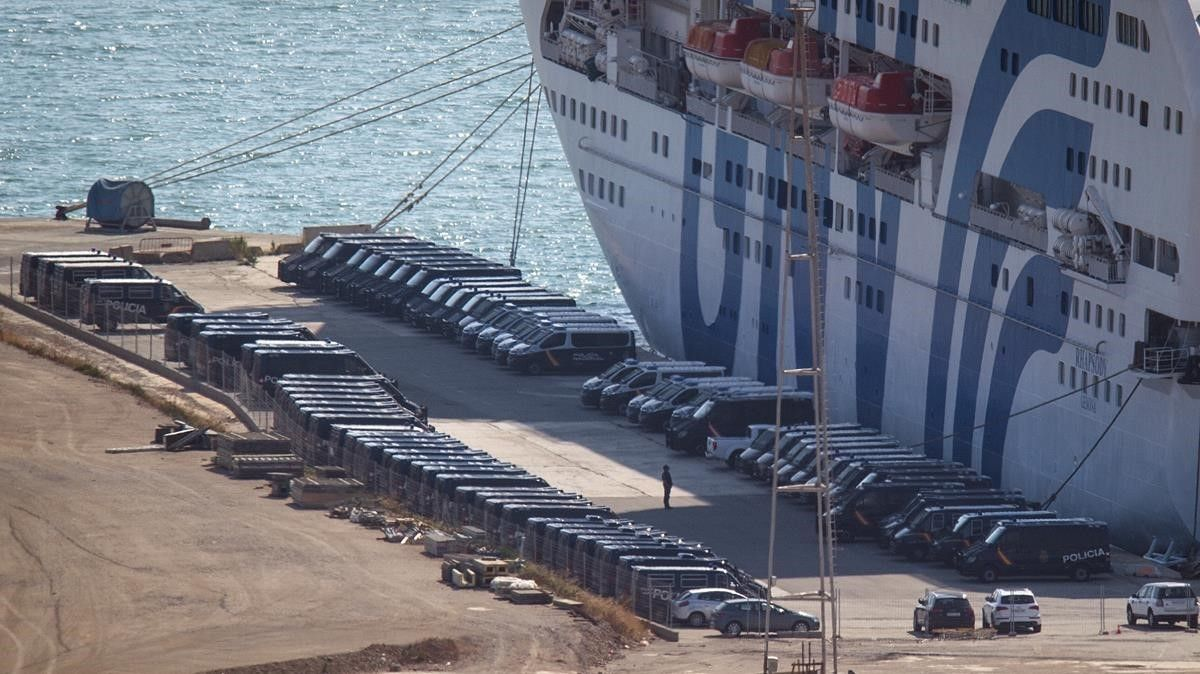 Furgonetas de la Policía Nacional, ante unbarco atracado en el puerto de Barcelona para alojar a policías y guardias civiles