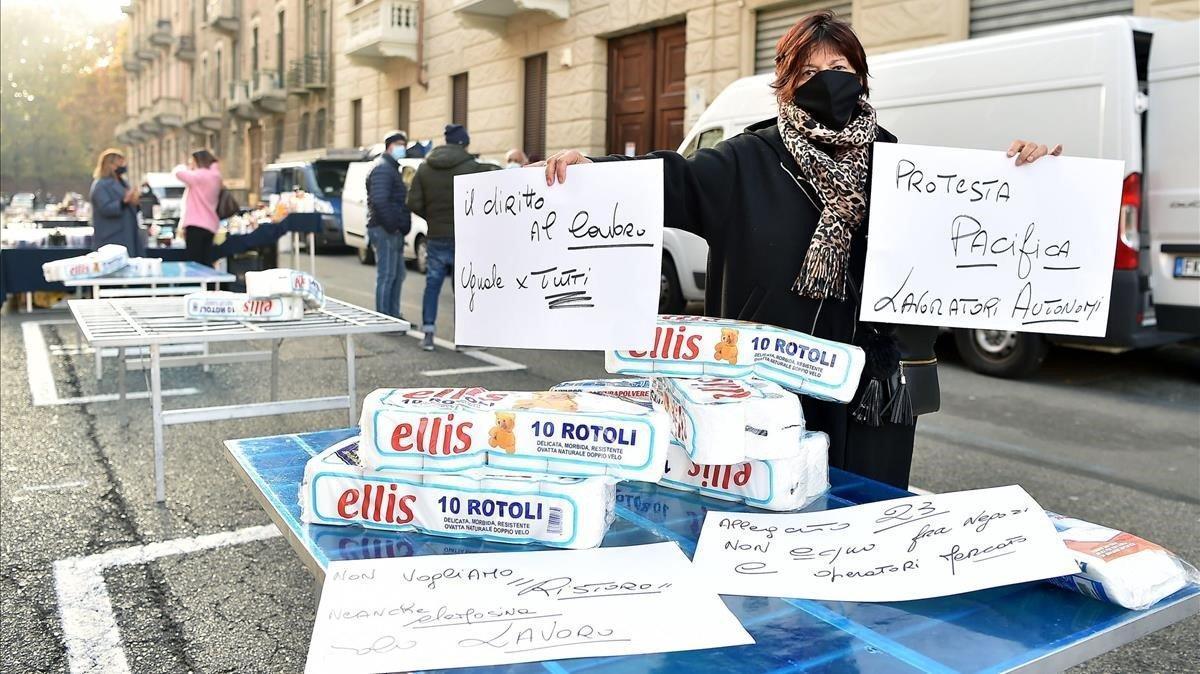 Vendores de ropa de un mercadillo protestan contra las medidas de confinamientomostrando papel de vater en Turín.