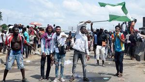 Un manifestante ondea una bandera nacional nigeriana detrás de las barricadas montadas en la autopista Lagos-Ibadan para protestar contra la brutalidad policial, el 21 de octubre.
