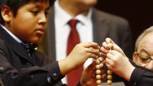 Dos niños ensartan las bolas de los números premiados de la Lotería de Navidad 2016.