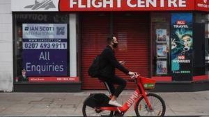 Un ciclista pasa por delante de una agencia de viajes en Londres.