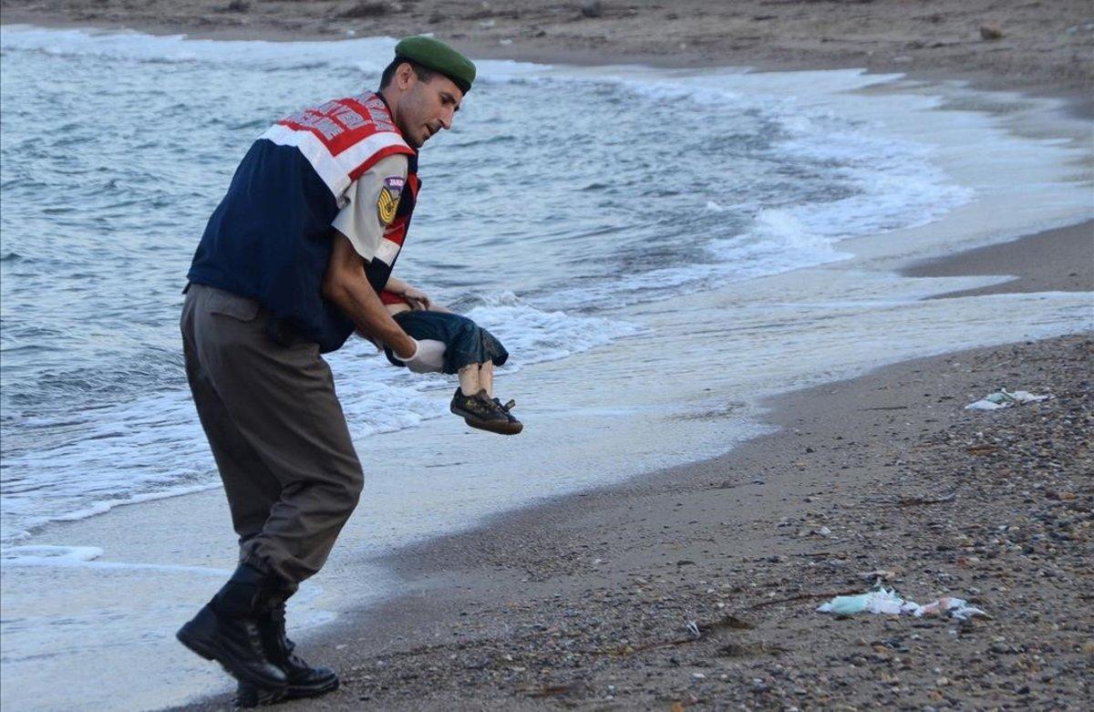 Un agente sostiene el cuerpo del pequeño Aylán.