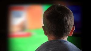 Un niño mira atentamente la televisión.
