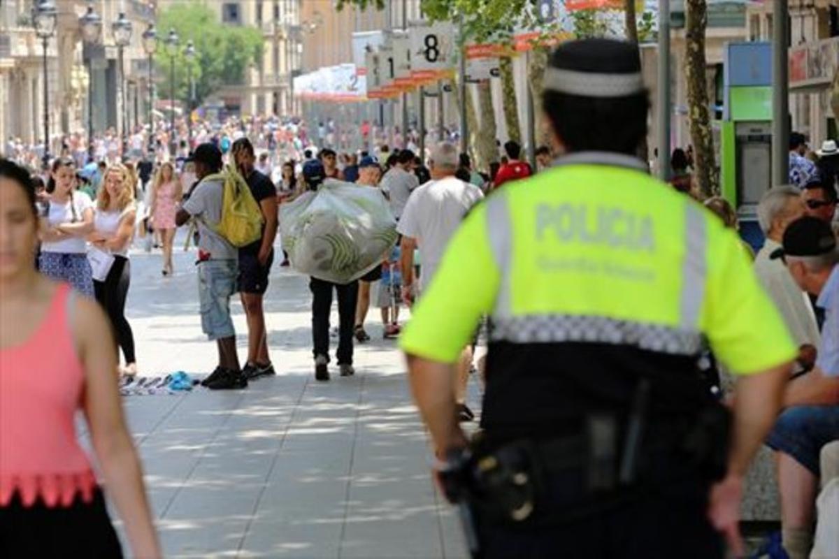 Un guardia urbano se acerca a unos manteros en Portal de l'Àngel, en una imagen de archivo.