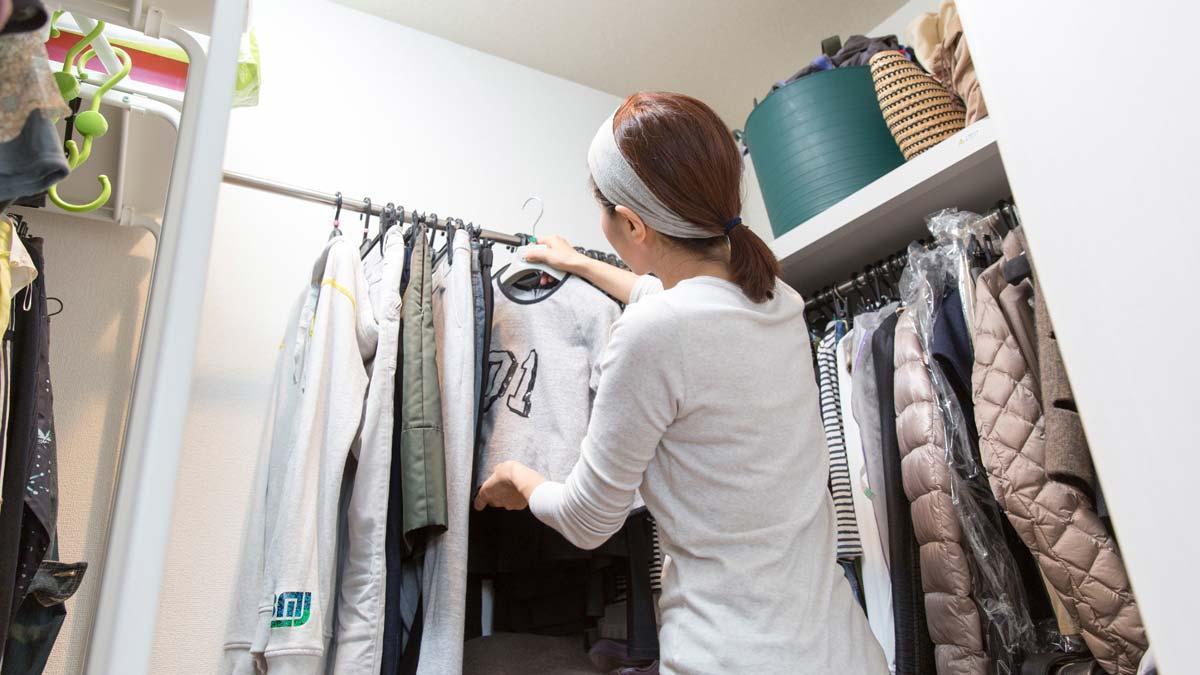 Una mujer ordena ropa en su armario.