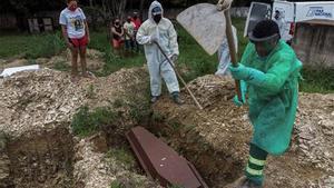 Familiares observan el entierro de un joven de 28 años muerto por coronavirus, en el cementerio Despraiado en Cuiabá, capital de Mato Grosso (Brasil).