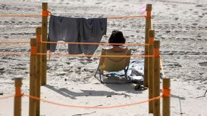 Una mujer sentada en la playa.