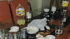 Imagen de la mesa de uno de los apartamentos con diversas botellas vacías y vasos.