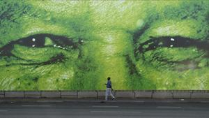 Un hombre pasa en frente de un gigante mural del histórico presidente sudafricano, Nelson Mandela.