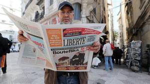 Un hombre lee un diarioen Argel este miércoles con la noticia en portadade la dimisión deButeflika.