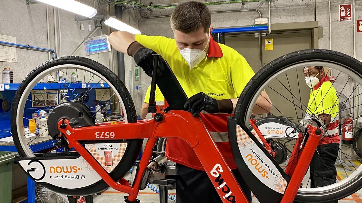 Un operario del Bicing introduce la batería en una bicicleta mecánica que pasará a ser eléctrica