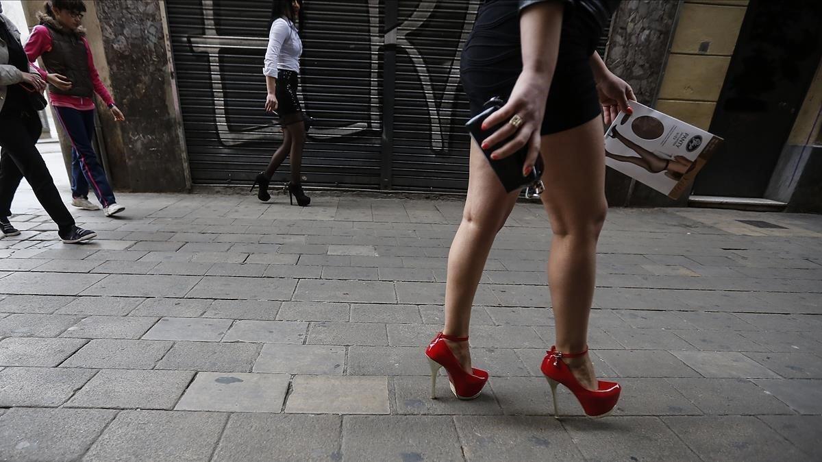 Una mujer camina por el Raval de Barcelona.