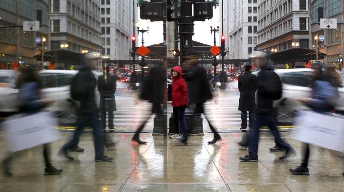 Personas de compras, reflejadas en el escaparate de una tienda en Chicago.