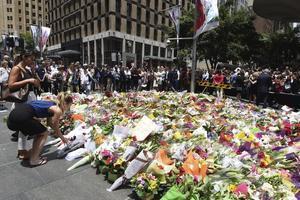 Centenars de ciutadans han anat al cafè on van tenir lloc els fets per dipositar rams de flors i missatges de condol.