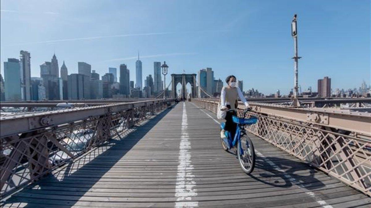 Una ciclista con mascarilla en el puente de Brooklyn de Nueva York.