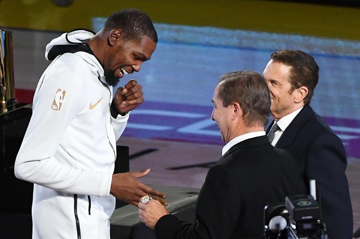 Kevin Durant recibe el anillo de campeón de la NBA de manos de Joe Lacob, uno de los propietarios de los Warriors