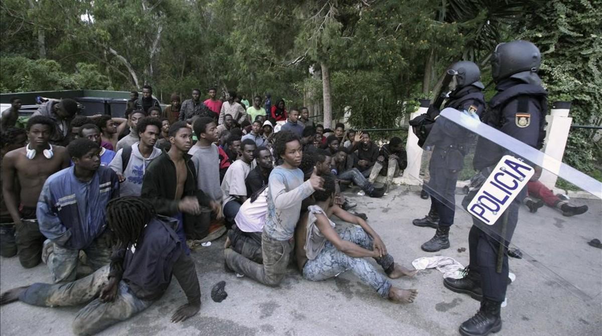 Inmigrantes retenidos tras saltar la valla en Ceuta el pasado febrero.