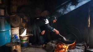 Una mujer fríe patatas en su vivienda en el barrio marginal construido junto al cementerio de Ghoraba, en Trípoli.