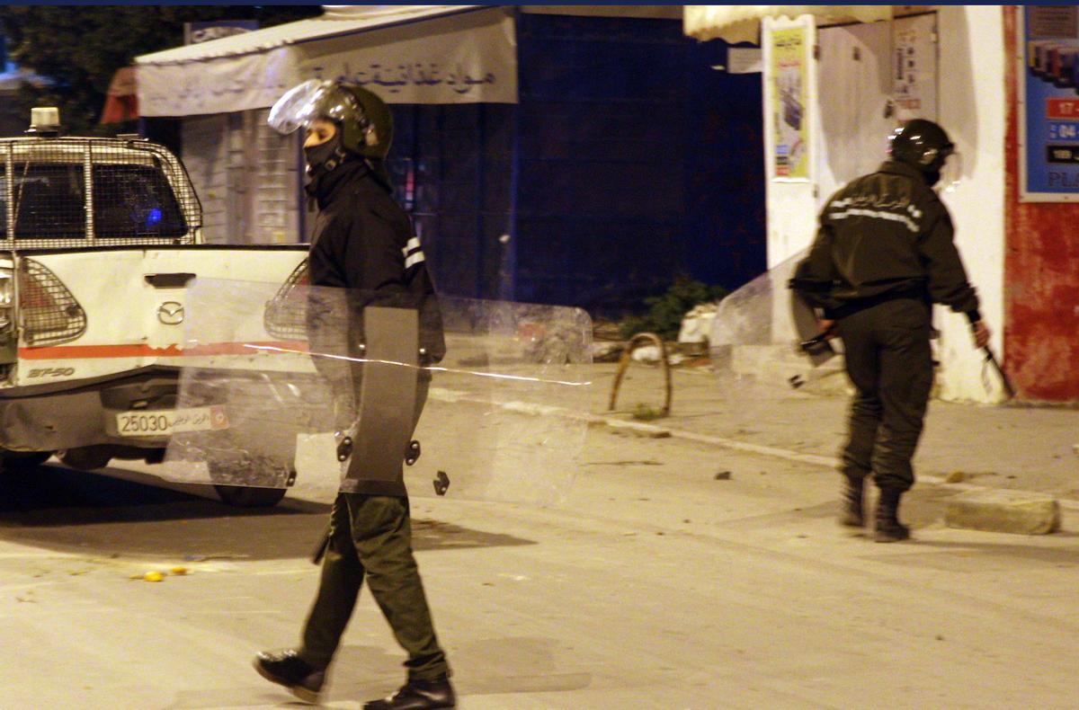Dos policías durante los disturbios en Ettadhamen, un suburbio de la capital de Túnez.