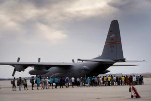 Afganos evacuados de Kabul en un avión de las fuerzas aéreas norteamericanas son transportados desde la base aérea de Torrejón de Ardoz.