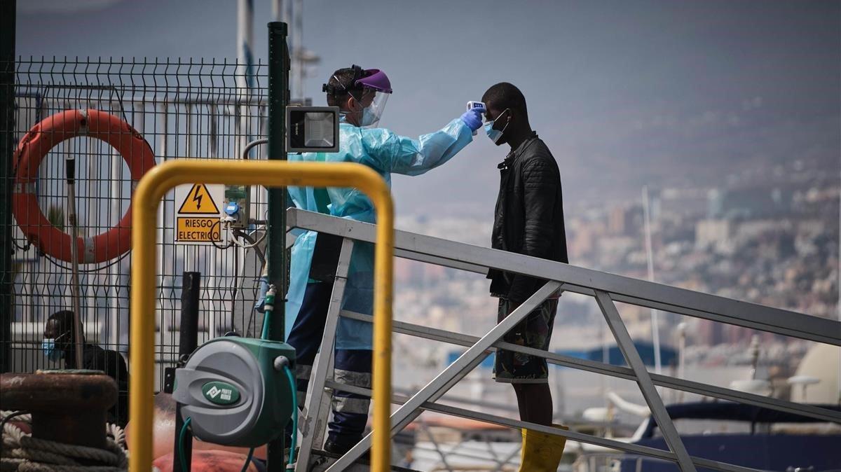 Un agente toma la temperatura a un joven recién llegado a Canarias.