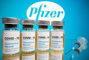 FILE PHOTO: Vials with a sticker reading, COVID-19 / Coronavirus vaccine / Injection only and a medical syringe are seen in front of a displayed Pfizer logo in this illustration taken October 31, 2020. REUTERS/Dado Ruvic/Illustration/File Photo