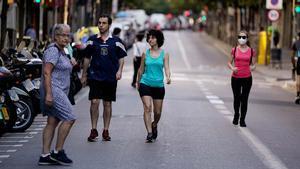 Peatones caminan y practican deporte en la Via Laietana de Barcelona, cerrada al tráfico. En la foto, la calle de Gran de Gràcia, también sin coches.