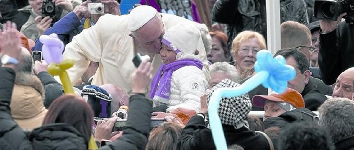 Bergoglio besa a un niño desde el papamóvil,en la plaza de San Pedro del Vaticano, esta semana.
