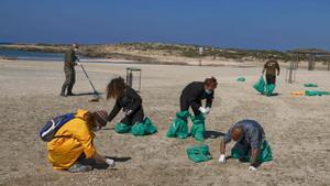 Un grupo de voluntarios israelís limpian de restos de petróleo la playa de  HaBonim, al sur del puerto de la ciudad de Haifa. -