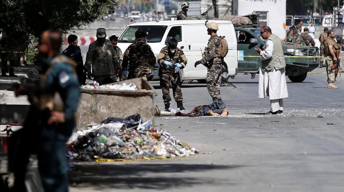 Fuerzas de seguridad afganas junto a un cadáver tras el mortífero ataque suicida en Kabul.