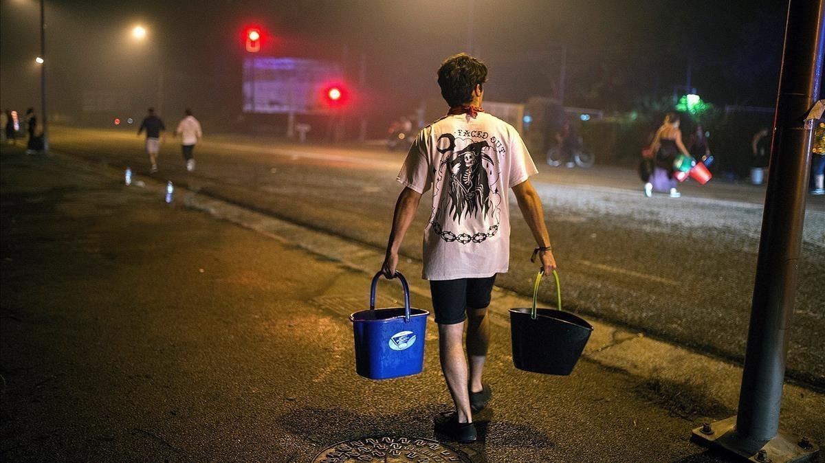Un hombre porta dos cubos de agua para ayudar a sofocar uno de los focos declarados en el centrode Vigo.