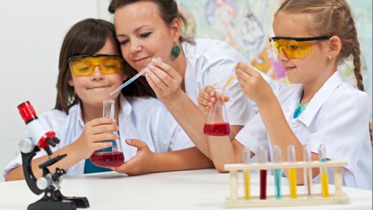 Una mujer y dos niñas realizan experimentos científicos.