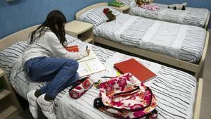 Una joven, en una imagen de archivo, tumbada en la cama en un centro de acogida.