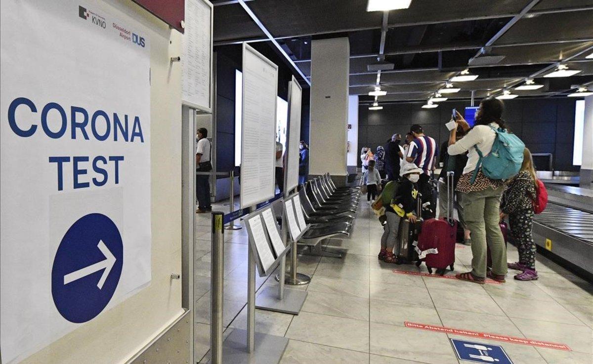 Pasajeros recién llegados a Alemania esperan para realizarse un test de coronavirus en el aeropuerto de Dusseldorf, el lunes 27 de julio.