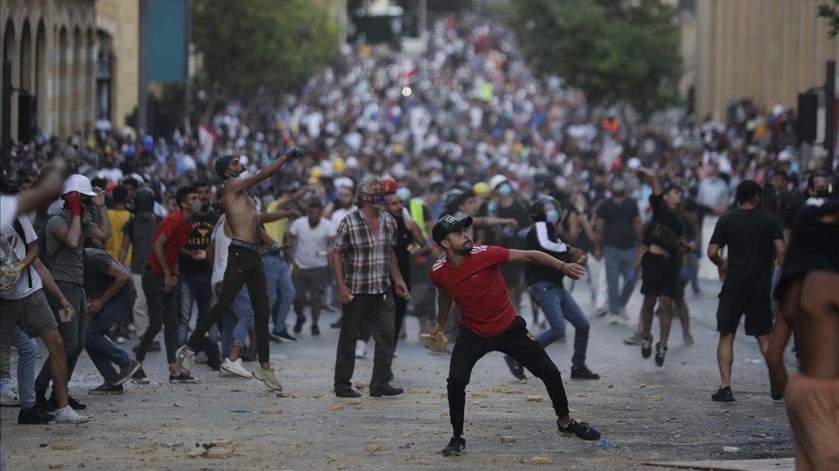 Los manifestantes tiran piedras contra la policía, este domingo en Beirut.