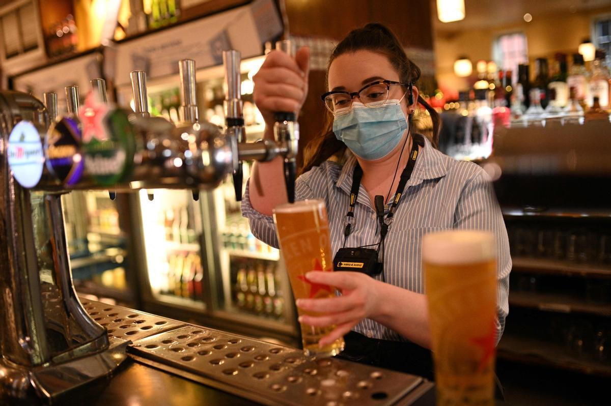 Una empleada de un pub de Manchester sirve una cerveza de barril.