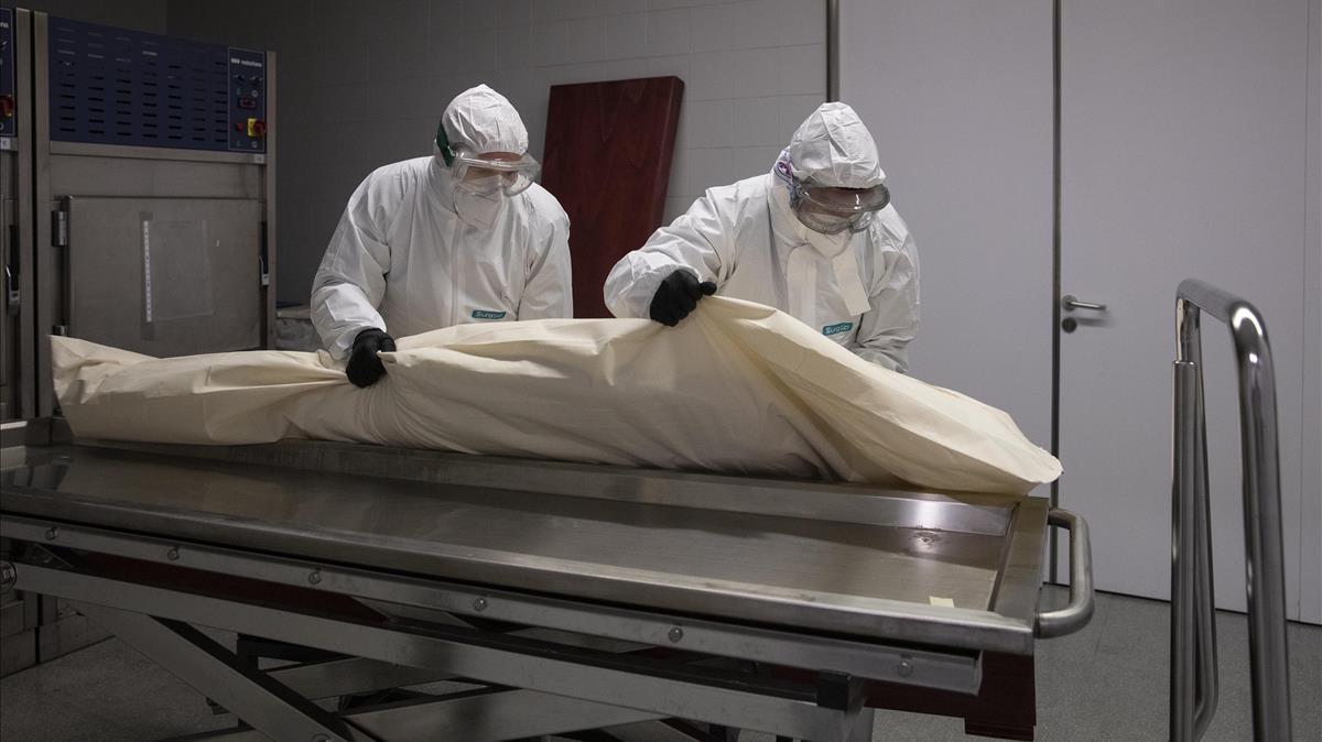 Al llegar al hospital de Mataró, los funerarios recogen el cuerpo de la morgue, que ya viene envuelto en una bolsa de plástico. De allí lo colocan directamente en el ataúd, que queda sellado para evitar contagios.