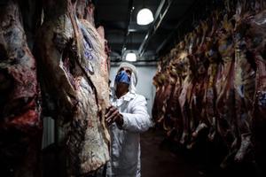 Empleados de una empresa frigorífica trabajan con carne de vacuno, en una planta de Buenos Aires.
