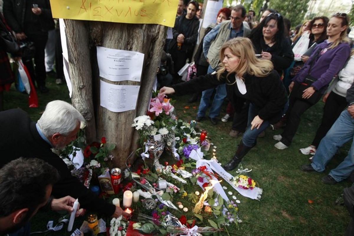 Varios ciudadanos colocan flores y velas en el lugar donde se suicidó el jubilado, el miércoles, en la plaza Sintagma, en Atenas.