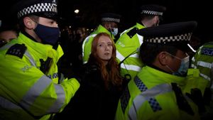 La Policía Metropolitana de Londres se lleva a una mujer arrestada tras los incidentes.
