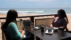 Dos mujeres, en una terraza de la playa de L' Arrabassada de Tarragona.