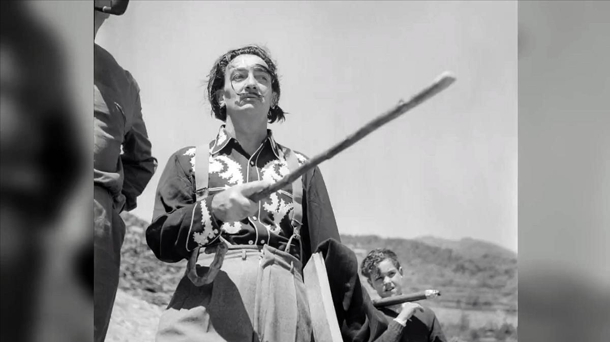 Dalí con uno de sus bastonesy el niño Joan, cargando el trípode de Francesc Català-Roca, camino de Portlligat, en Cadaqués.