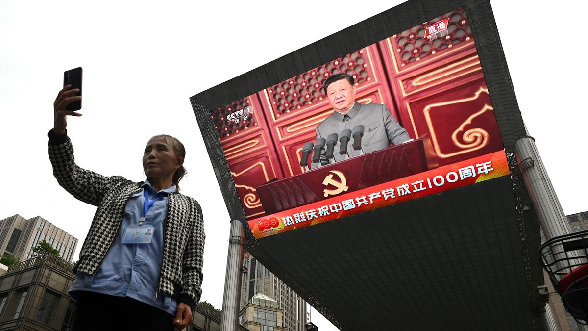 Una mujer se hace un 'selfie' con la alocución del presidente chino Xi Jinping de fondo.