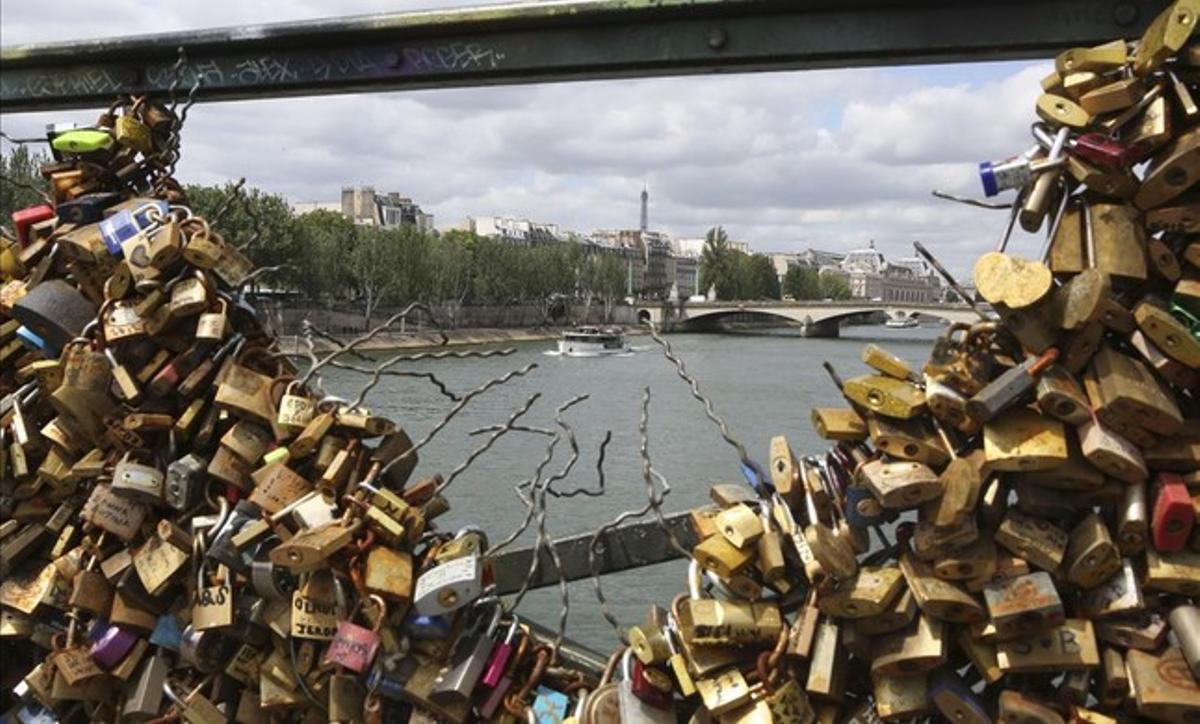 La Torre Eiffel vista a través de una de las barandillas del puente de las Artes, en París. Las autoridades han empezado a retirar los candados el lunes 1 de junio.