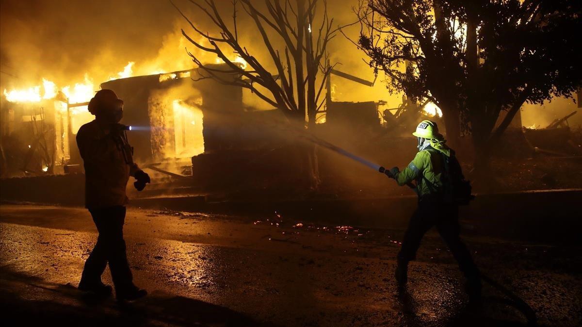 Los bomberos combaten las llamas que prenden en una vivienda en Los Ángeles, este lunes.