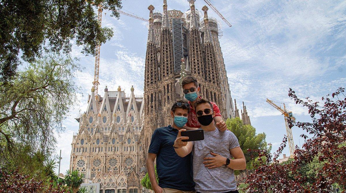 Tres jóvenes con mascarilla se hacen un selfi ante la Sagrada Família, el pasado 10 de julio.
