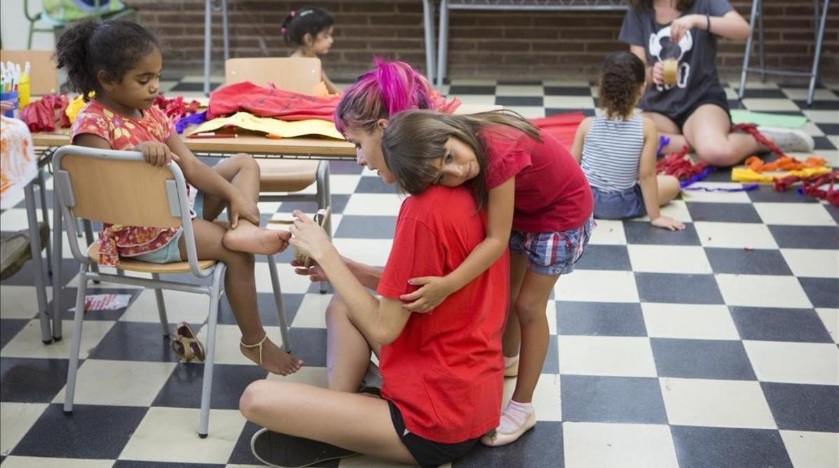 Una niña abraza a su monitora en el campamento urbano de Baró de Viver.